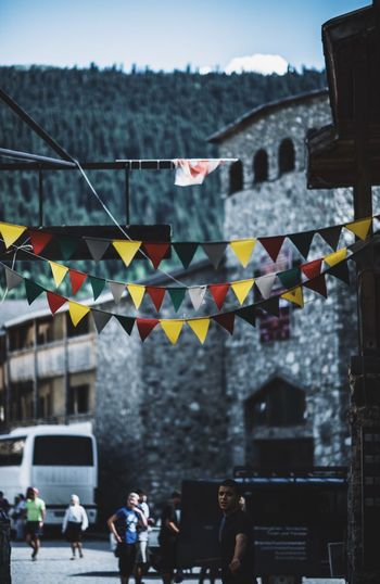 Colorful bunting hanging against buildings in city