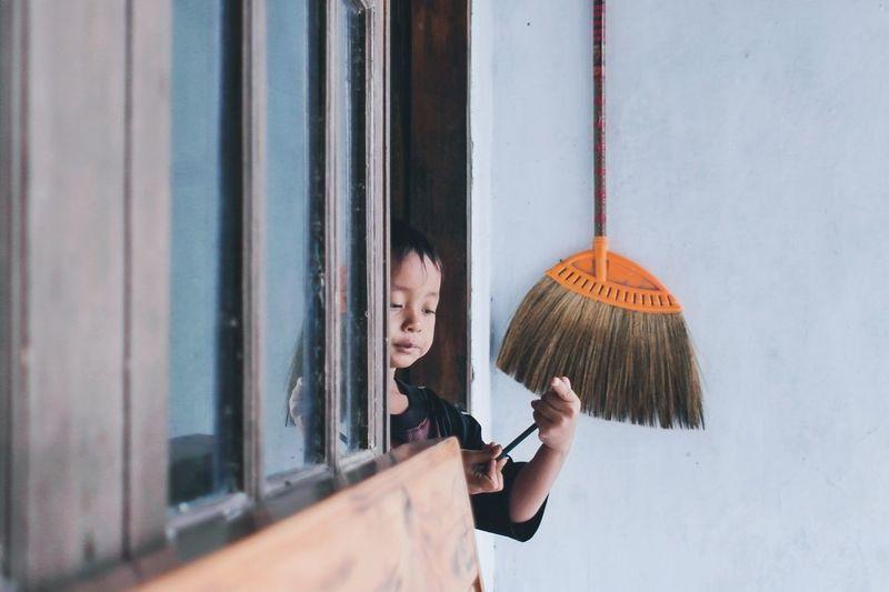 Portrait of a boy standing by window