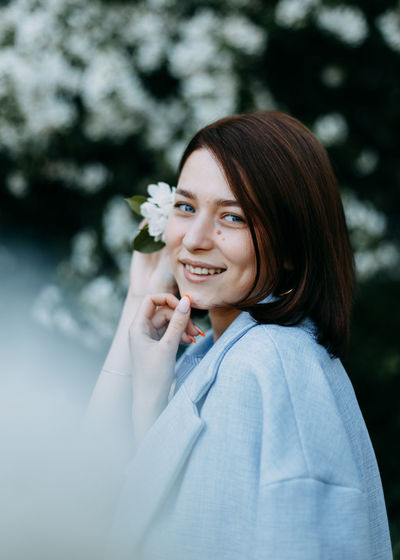Portrait of happy smiling young woman with flower near her head in blooming park