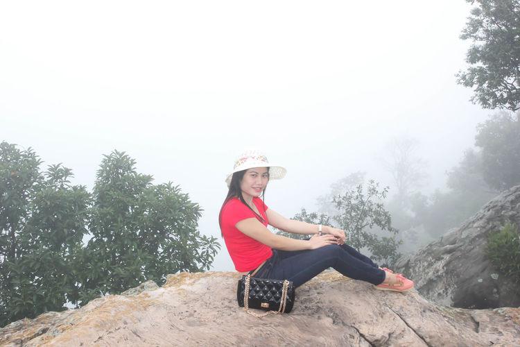Portrait of woman sitting on rock against sky