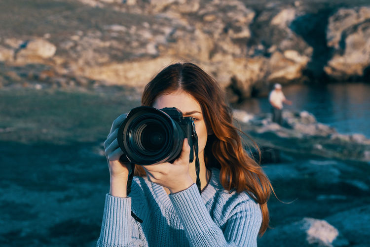 Portrait of young woman photographing camera