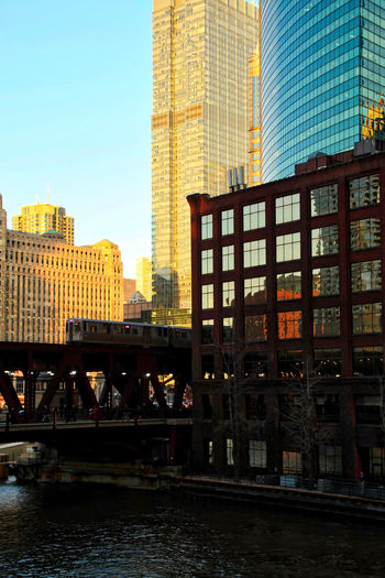 Chicago downtown during evening commute on a late February winter evening. El train passes over Chicago River. Waysofseeing Chicago Chicago River Chicago El Chicago Loop Commuter Downtown Chicago Elevated Track Reflection Transportation Architecture Building Exterior Built Structure City Cityscape Commuter Train Day Elevated Train Lake Street Modern No People Outdoors Sky Skyscraper Travel Destinations Water