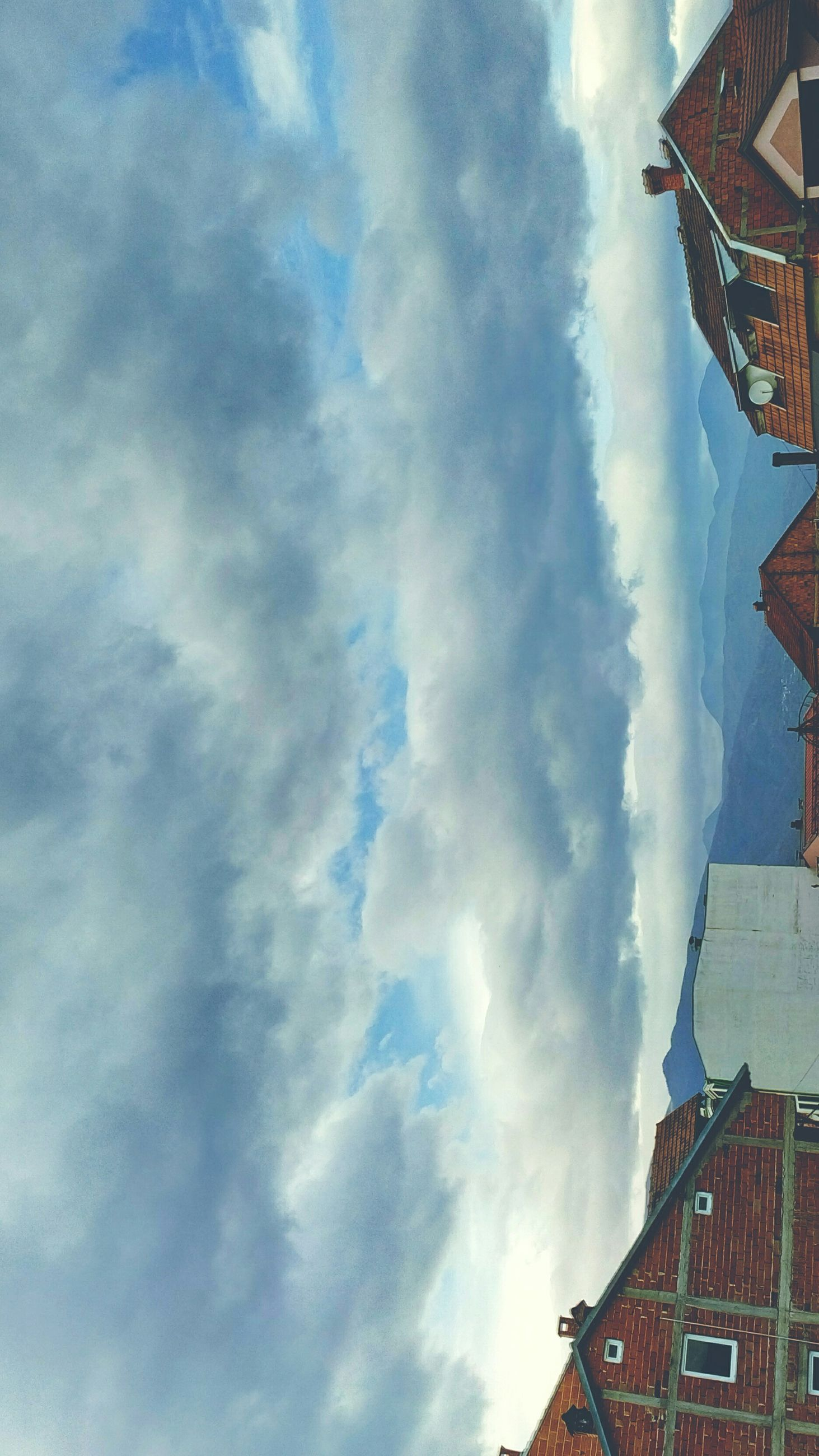 architecture, building exterior, built structure, sky, cloud - sky, low angle view, cloudy, cloud, roof, residential structure, city, residential building, building, outdoors, house, day, no people, high section, weather, blue