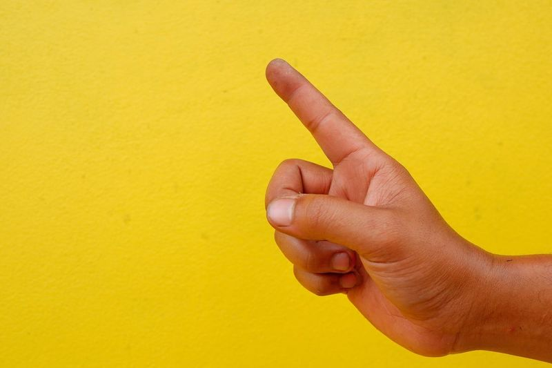 Cropped hand pointing against yellow wall
