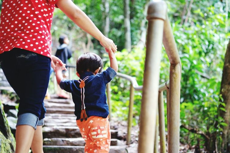 Rear view of mother climbing steps while holding hands with boy