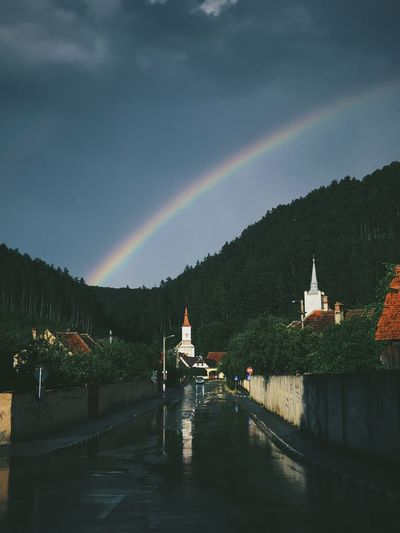 Scenic view of rainbow against sky during rainy season