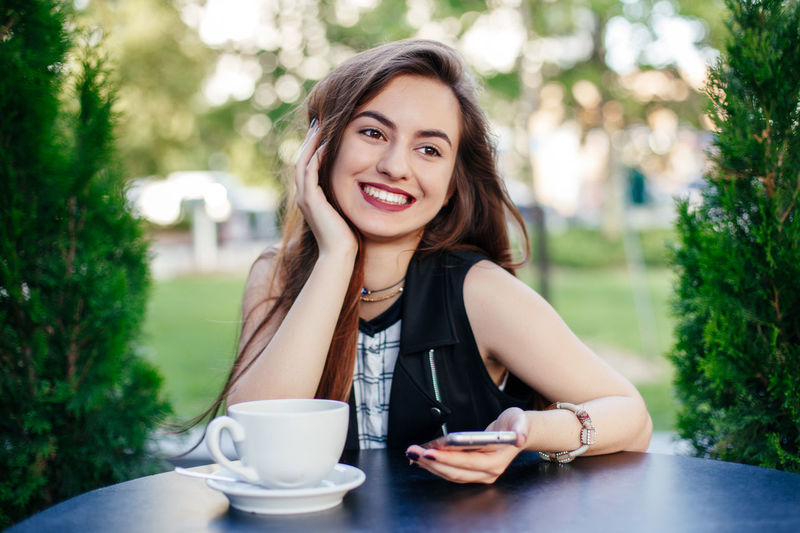 Smiling young woman using smart phone at outdoor cafe