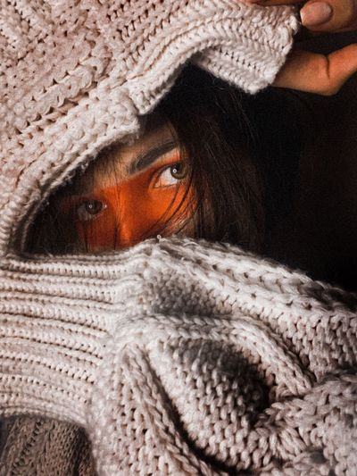 Close-up portrait of young woman hiding in snow