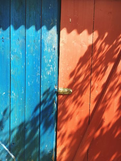 Full Frame Shot Of Orange And Blue Closed Door On Sunny Day