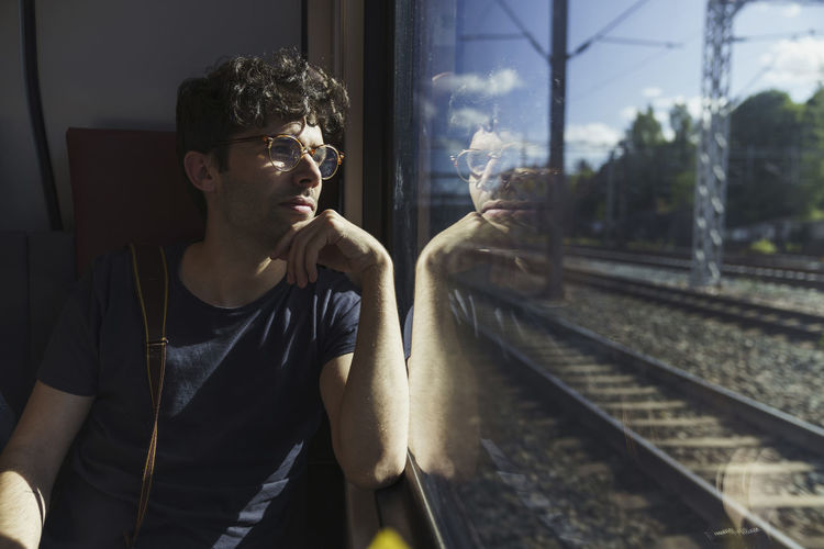 Young man looking through window at railroad tracks