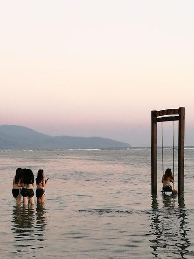 Women looking at friend swinging in sea against sky