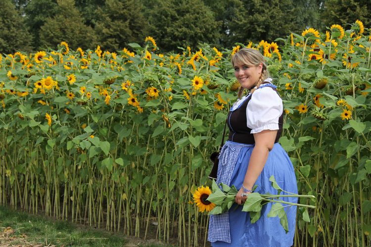 Portrait of woman in dirndl dress standing at sunflower field
