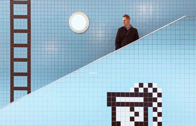 Man looking away while standing against tiled wall
