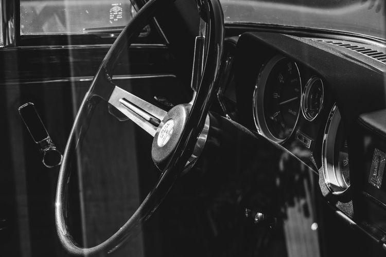 Steering wheel of vintage car seen from window glass