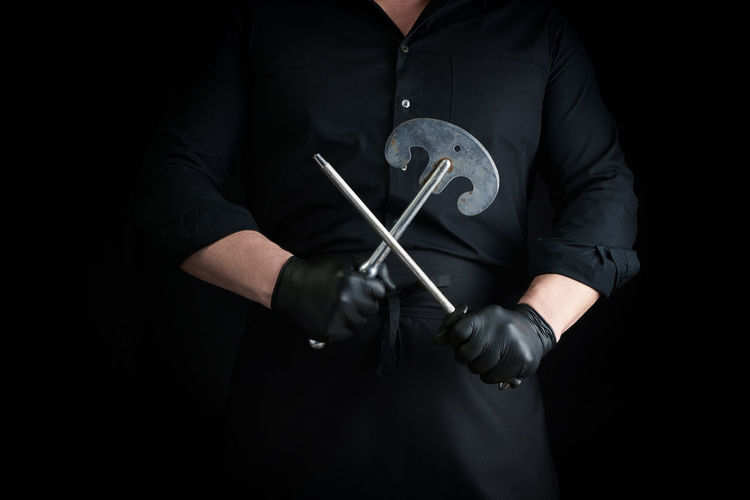 Midsection of man holding tools against black background