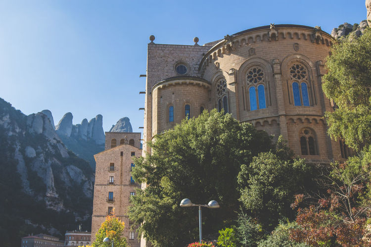 Low angle view of buildings against clear sky at santa maria de montserrat abbey