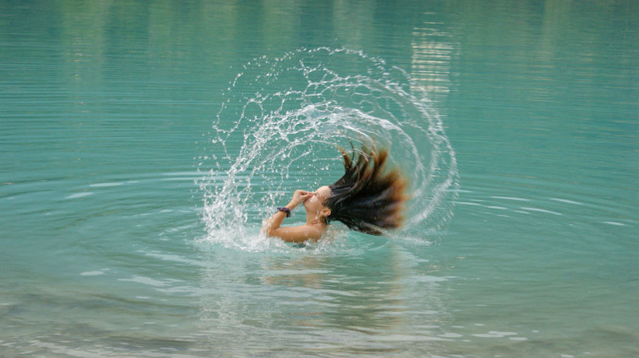 Side view of young woman tossing wet hair in sea
