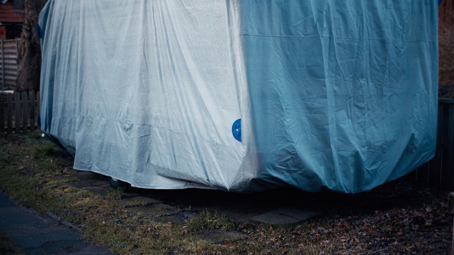 Close-up of cover over camper trailer on land in backyard