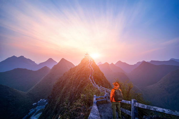 Rear View Of Man Looking At Mountains Against Sky During Sunset