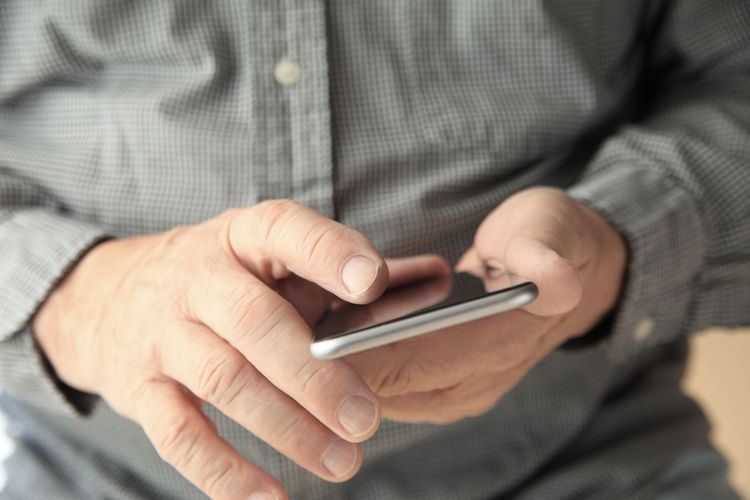 Man with his cellphone Casual Clothing Cell Phone  Close-up Device Fingers Front View Hands Holding Indoors  Man Midsection Natural Light Reflective Surface Searching Senior Using Technology Smartphone Technology Unrecognizable Person Using Internet