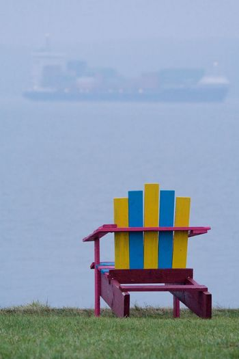 Colorful chair at riverside Absence Blue Chair Colorful Empty Foggy Grass Green Purple Relaxation Relaxing Relaxing Moments River Riverside Sea Ship Yellow