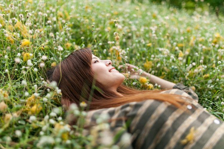 Smiling woman lying on field