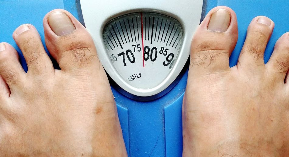 Cropped legs of person on weight scale