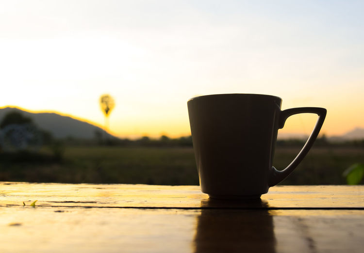 coffee cup with colourful light in sunset time Food Object Colorful Natural Beautiful Copy Space Sunset Light Evening Sky View Coffee Time Lifestyles Outdoors Drink Sunset Sunlight Rural Scene Close-up Food And Drink Coffee Pot Jug Frothy Drink Black Coffee Froth Art Mug Cappuccino Latte Froth Saucer