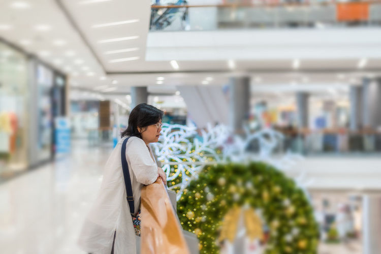 Woman Standing By Railing At Mall