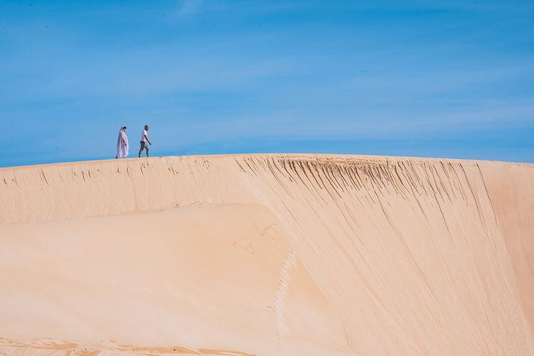 Couple walking along sand dune