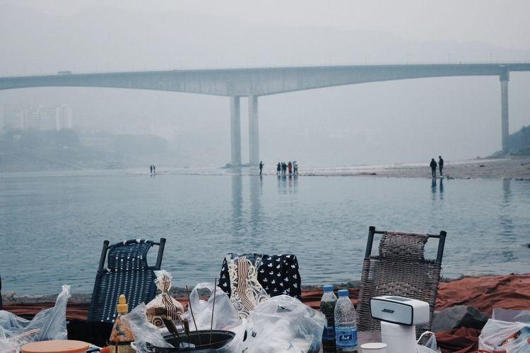 People on bridge over sea against sky