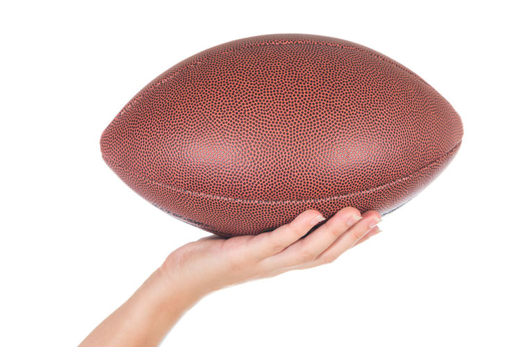 Cropped Hand Holding Rugby Ball Against White Background
