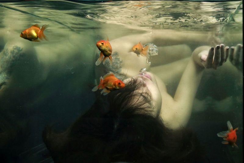 Shirtless woman in aquarium
