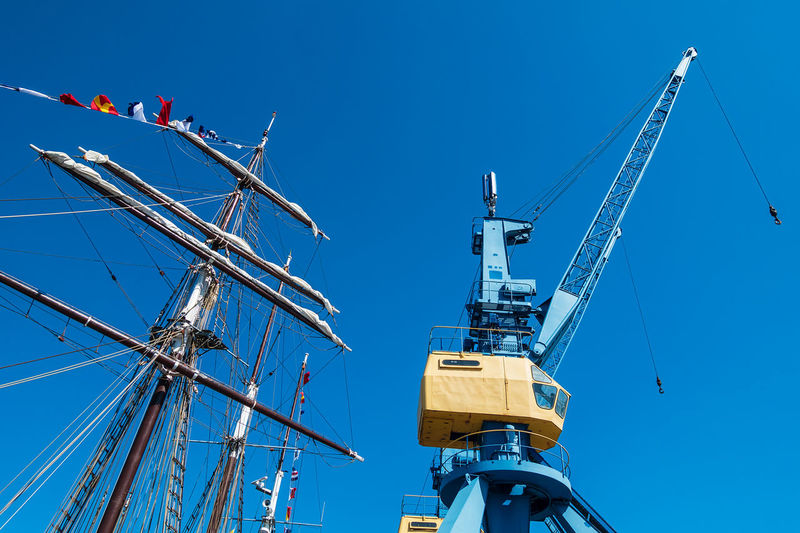 Low angle view of mast by crane against clear blue sky