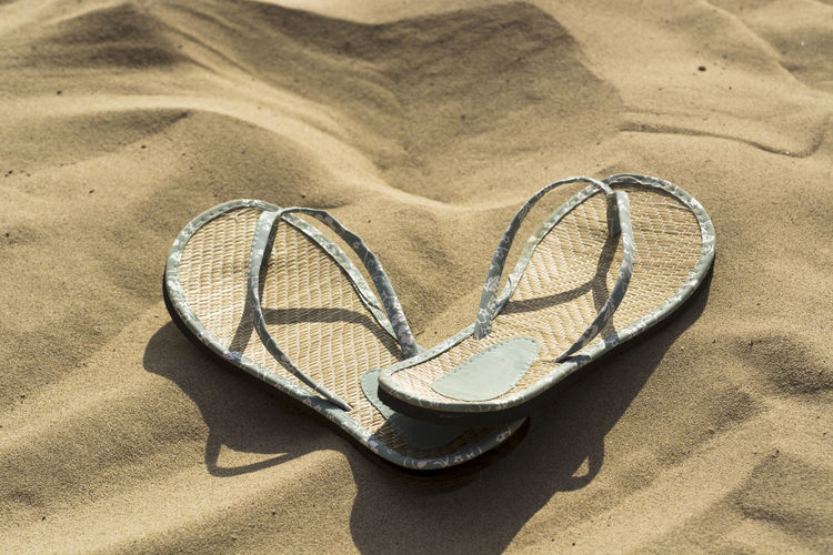 slippers of straw flip flops resting on the sand of the sea of Abruzzo Beach Close-up Day Flip-flop Heart Shape No People Outdoors Pair Sand Sunlight Vacations