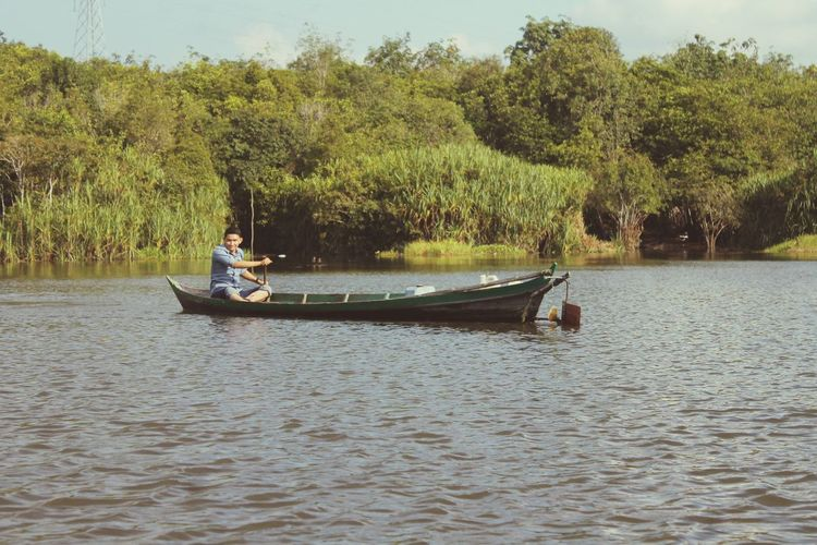 Man sitting in boat on lake against trees