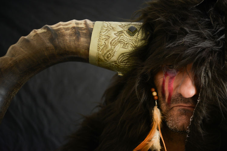 Portrait Of Mature Man With Face Paint Wearing Horn And Fur
