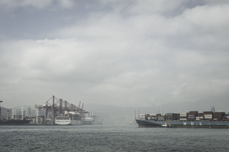 Container ship at commercial dock against cloudy sky