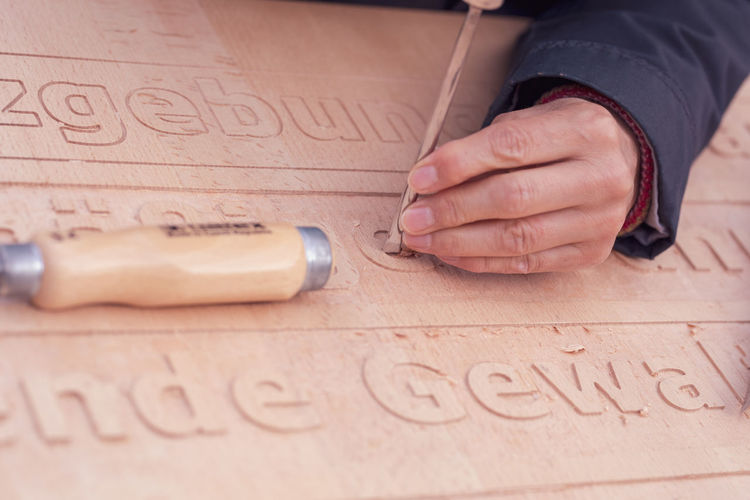 Cropped hand carving texts on wooden plank