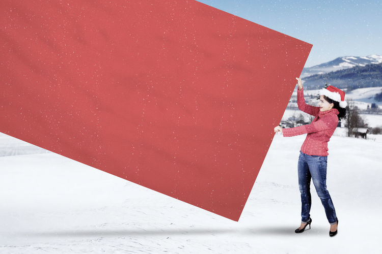 Full Length Of Woman Holding Blank Red Paper During Winter