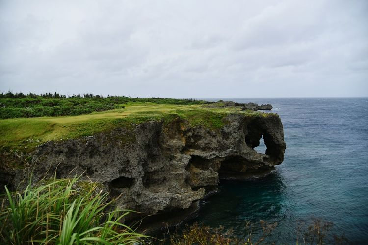 Rocky Cliff By Sea Against Cloudy Sky