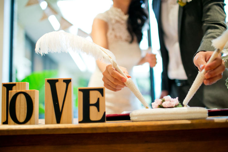 Close-up of newlywed couple signing the document with love text on table