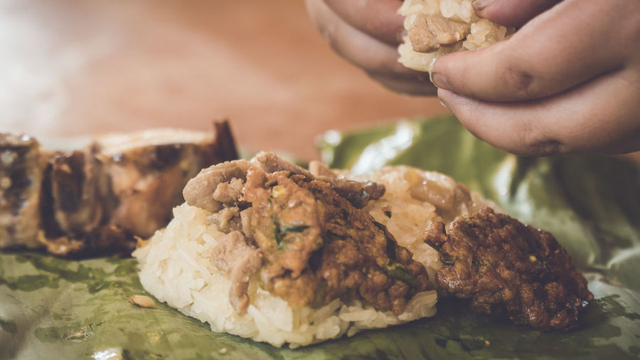 Close-up of hand eating food in banana leaf