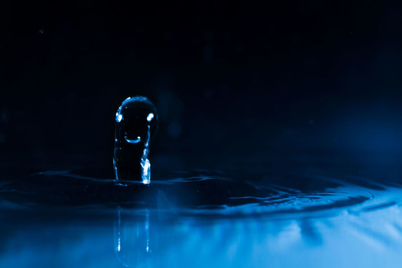 Close-up of droplet falling in water against black background