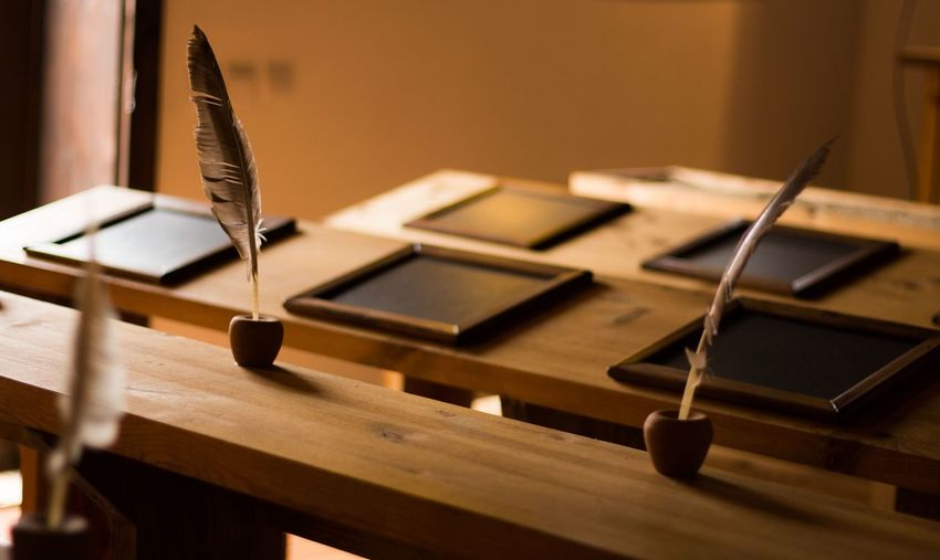 Writing Slates And Quill Pens On Desk In Classroom
