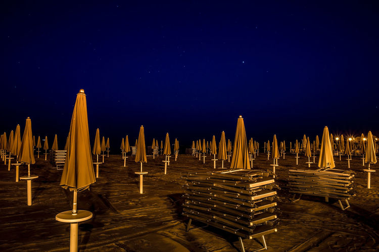 Sky No People Night Water Blue Star - Space Illuminated Tranquility Clear Sky Outdoors Tranquil Scene Beach Beachphotography Notte Spiaggia Ombrelloni Sdraio Beach Umbrella Umbrella Deckchairs Sea