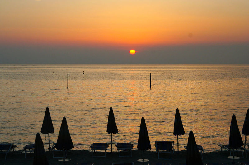 Tramonto sul mare Sunset Silhouettes Beach Beach Umbrellas Beauty In Nature Ombrelloni Scenics Sea Sea And Sky Sunset Tramontosulmare Vacations