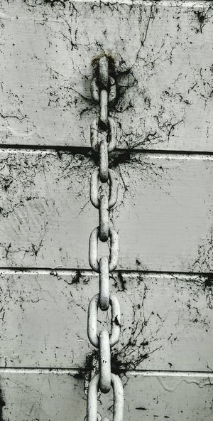 Close-up of chain on wooden wall