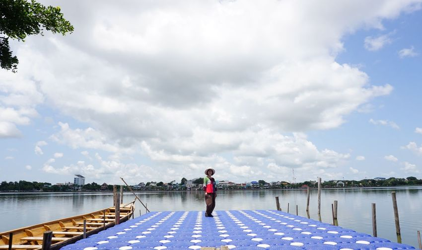 Woman standing on pier by lake against cloudy sky