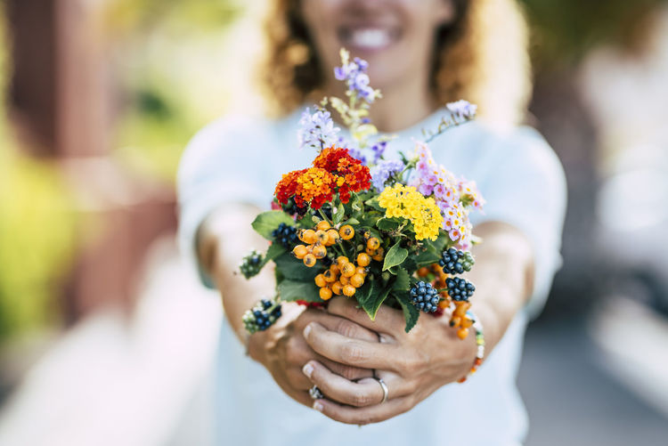 Midsection of smiling woman holding flowers
